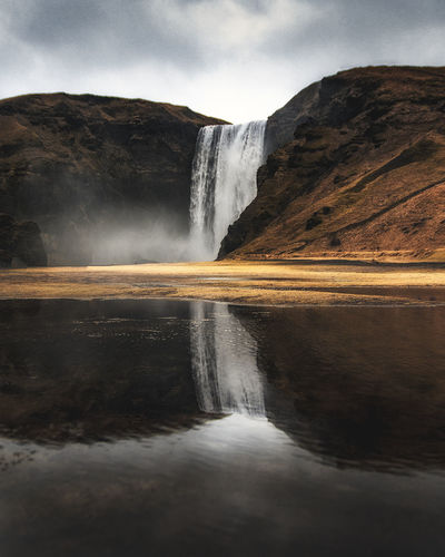 Reflecting on Iceland Beauty In Nature Colour Geology Iceland Iceland Memories Landscape Landscape_Collection Mist Mountain Nature No People Reflection Reflection Rock - Object Scenics Skogafoss Sky Tranquil Scene Travel Destinations Water Waterfall
