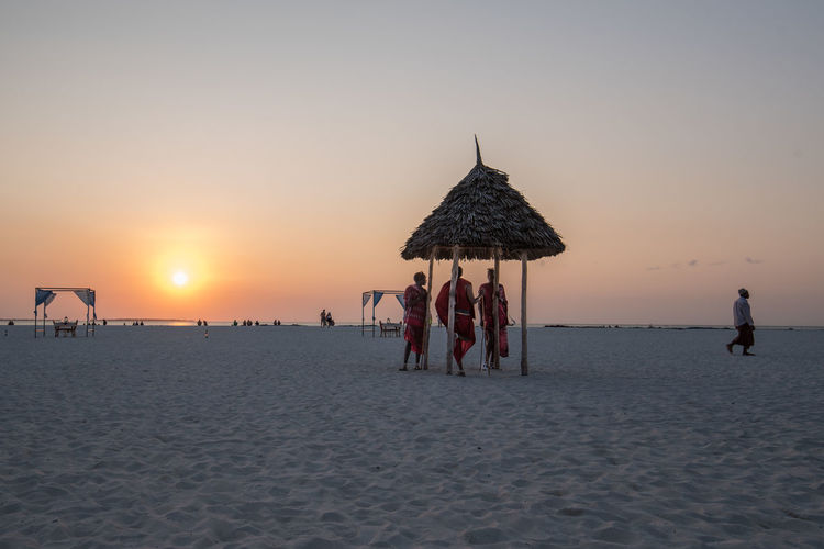 People Standing In Thatched Roof At Beach During Sunset