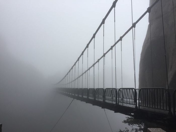 Bridge over river in foggy weather against sky