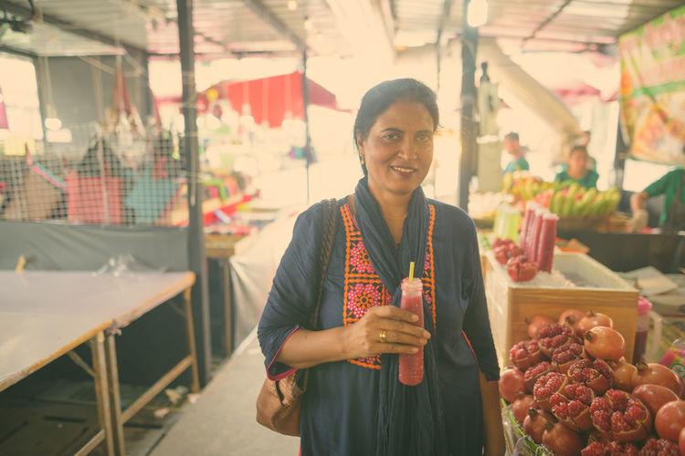 Woman drinking juice in market