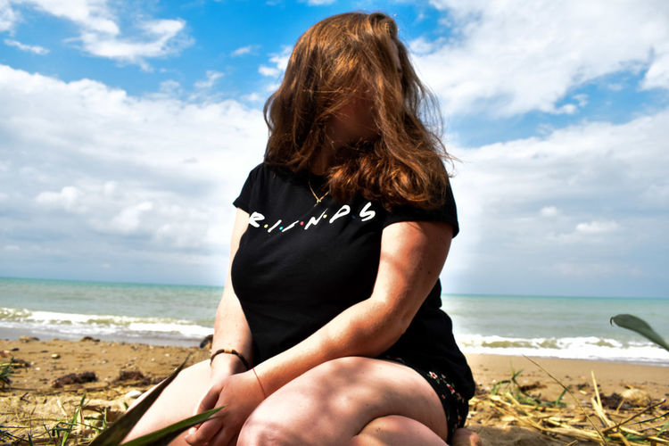 Woman with brown hair sitting at beach