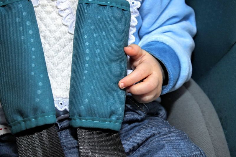 Midsection of baby wearing seat belt in car