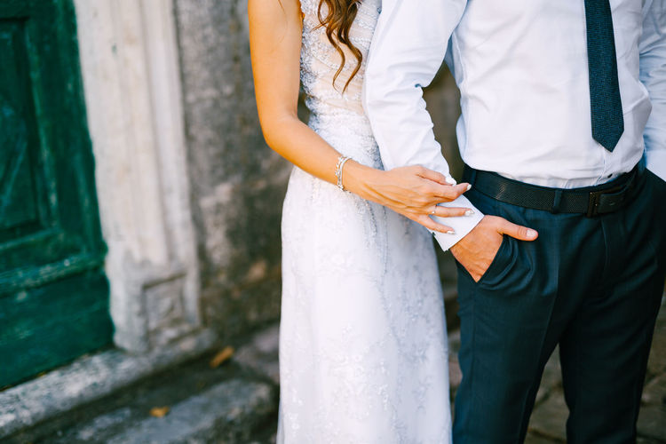 Rear view of couple standing against brick wall