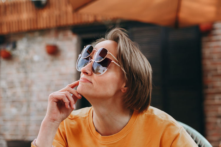 Smiling woman wearing various sunglasses