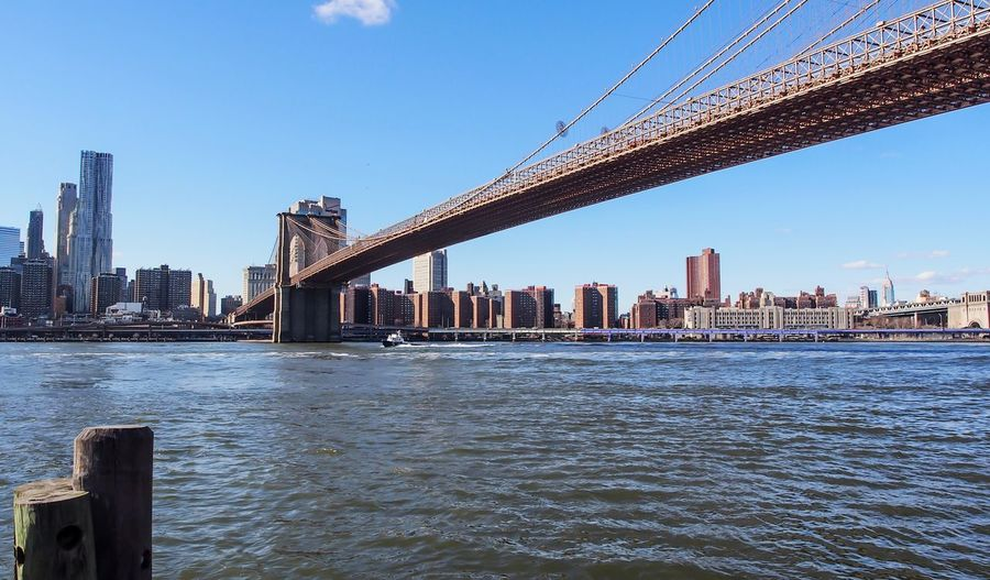 Low angle view of brooklyn bridge over east river in city