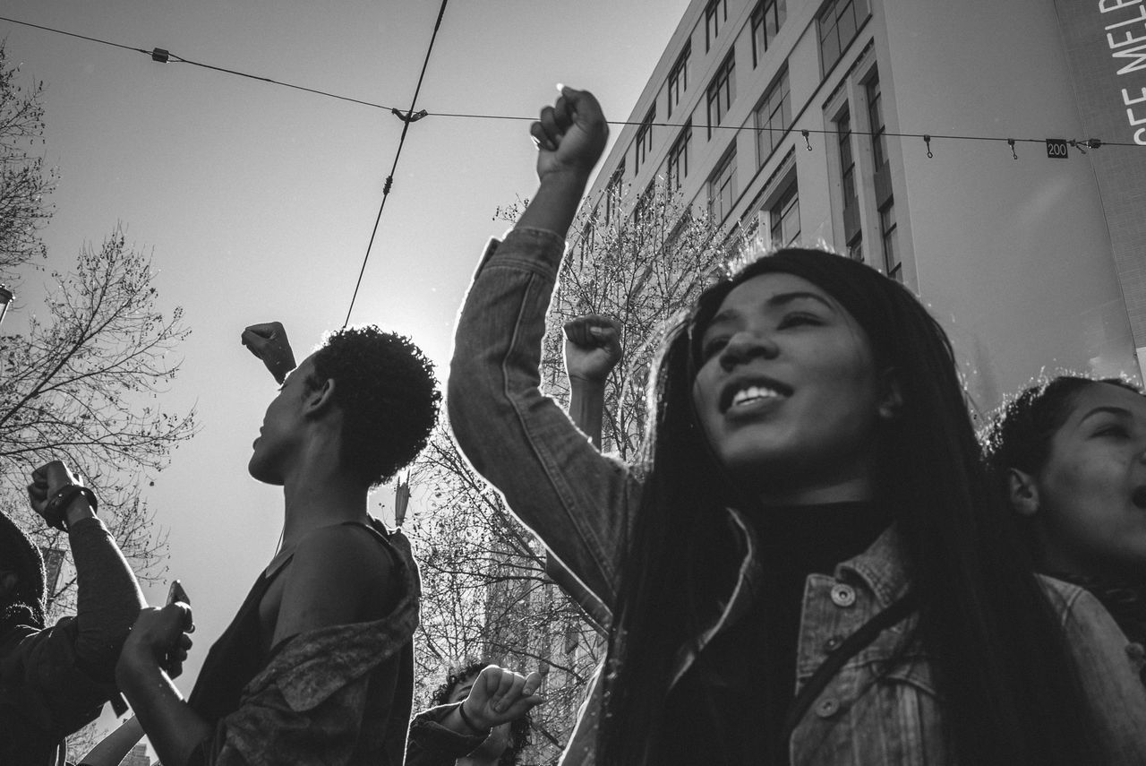 real people, arms raised, leisure activity, outdoors, lifestyles, fun, enjoyment, day, women, happiness, young women, holding, smiling, togetherness, low angle view, headshot, cheerful, crowd, young adult, human body part, sky, friendship, tree, human hand, people