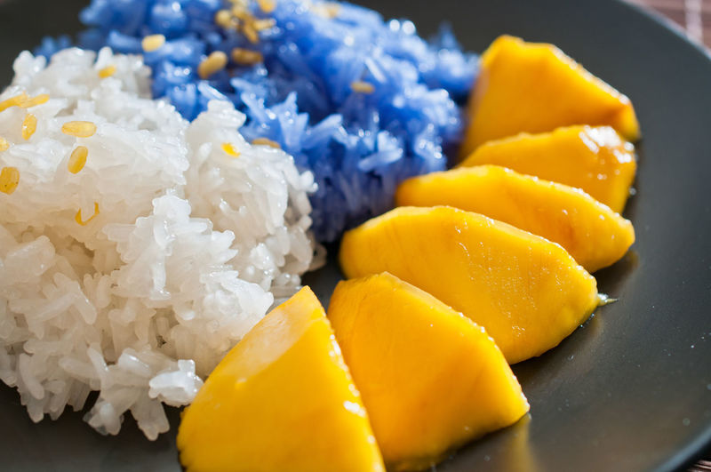 Close-Up Of White And Blue Rice With Mango Served In Plate
