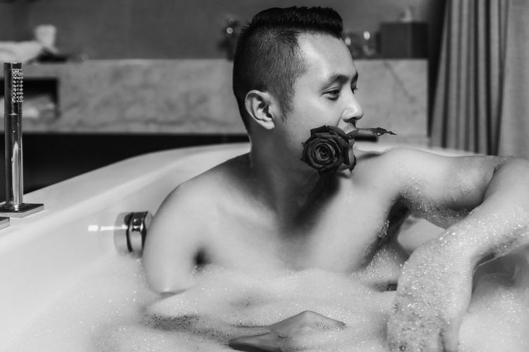 Shirtless man carrying rose in mouth while siting in bathtub