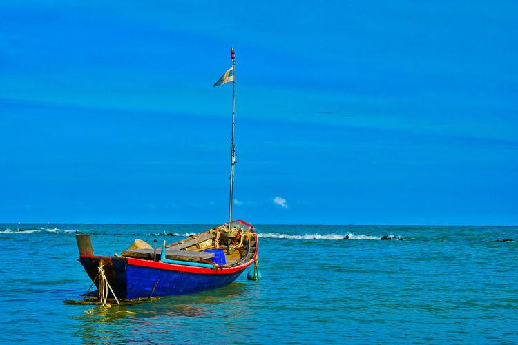 Boat moored in sea against blue sky