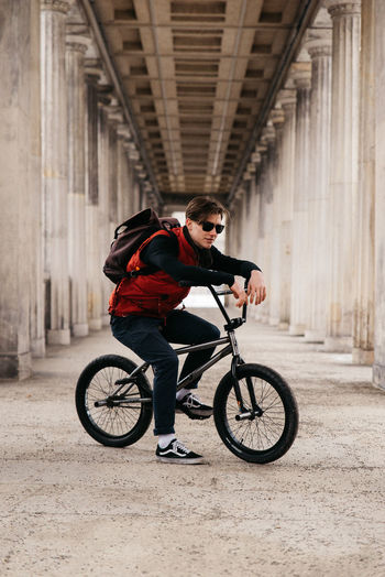 One Person Bicycle Architecture Transportation Full Length Young Adult Built Structure Lifestyles Leisure Activity Ride Real People Riding Mode Of Transportation Activity Sport Casual Clothing City Young Men Clothing Outdoors Architectural Column