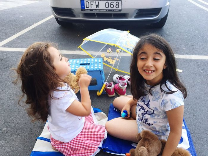 EyeEm Selects Sisters ❤ Picnic Time ♡ in Parking Lot Sisters Picnic Keep It Simple Keeping It Simple Girls Two People Childhood Transportation Real People Car Looking At Camera Sitting Togetherness High Angle View Child Portrait Lifestyles Smiling Leisure Activity Enjoyment Day Outdoors Friendship Bonding