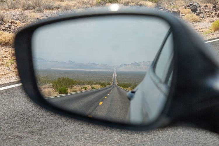 Reflection Of Road And Landscape On Side-View Mirror Of Car