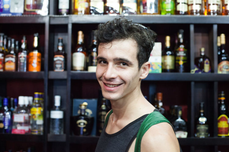 Portrait Smiling One Person Looking At Camera Bar - Drink Establishment Headshot Happiness Alcohol Indoors  Bottle Shelf Emotion Refreshment Adult Drink Young Adult Container Food And Drink Business Happy Hour Bar Counter Bartender Hairstyle Liquor Store