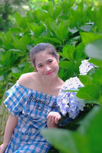 Portrait of young woman against blue flowering plants