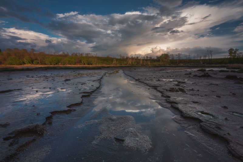 Surface level of wet land against sky during sunset