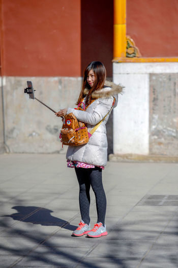 A young girl photographs selfie at Yonghegong Lama Temple in Beijing, China. ASIA Beijing Lama Temple Monastery Smoke Worshippers Adult Architecture Budhism Casual Clothing China City Day Front View Full Length Hair Hairstyle History Holding Lama Leisure Activity Lifestyles Music One Person Outdoors Phone Photography Prayer Real People Religion Selfie Standing Stick Temple Women Yonghe Yonghegong Young Adult Young Women
