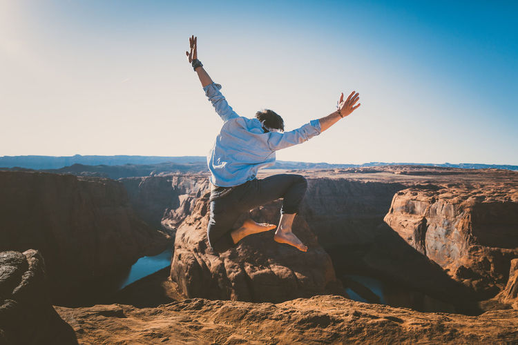 Man jumping on rock by mountain against sky