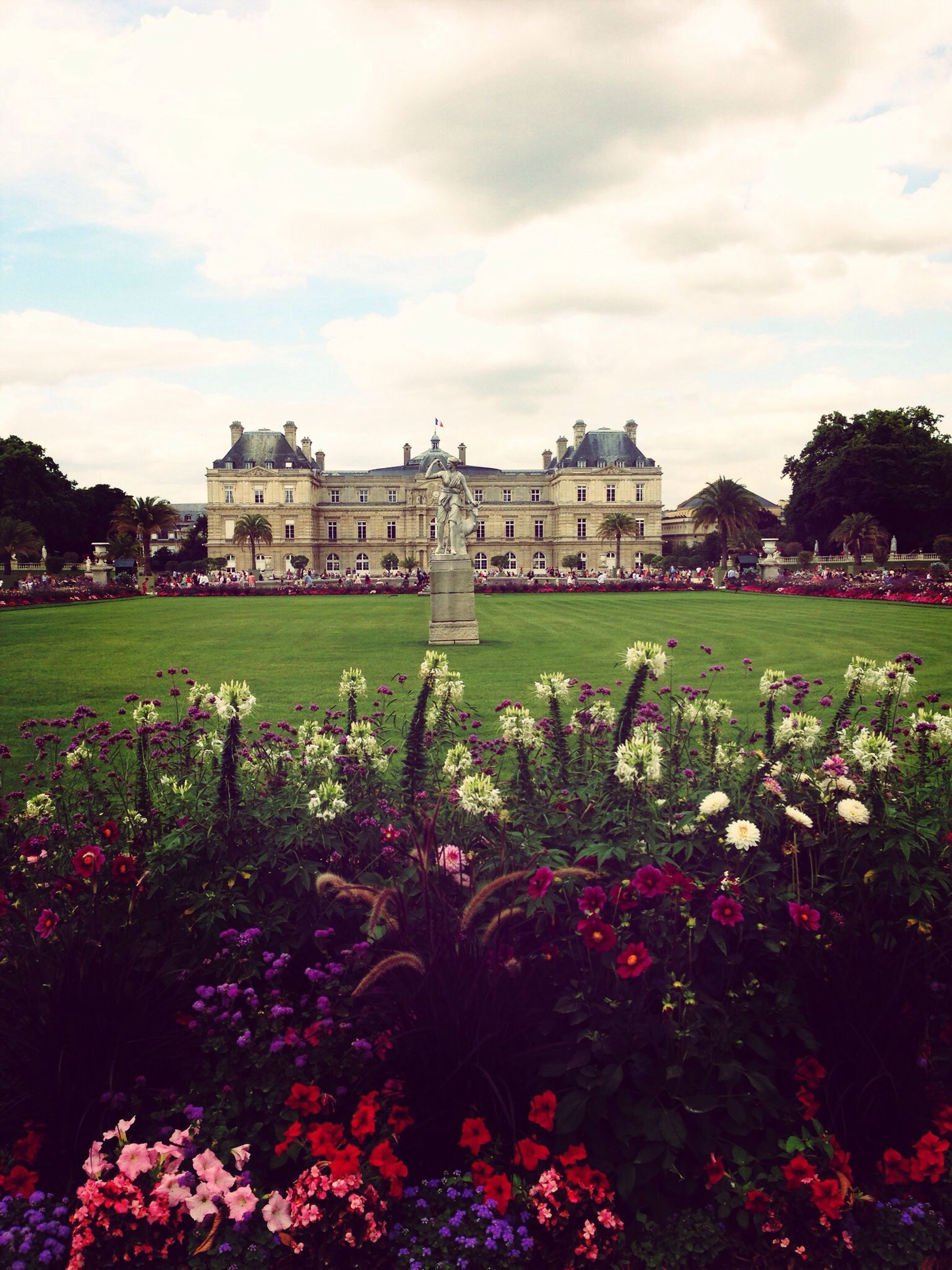flower, sky, grass, architecture, building exterior, cloud - sky, built structure, plant, growth, field, lawn, cloudy, cloud, freshness, green color, nature, formal garden, fragility, park - man made space, beauty in nature