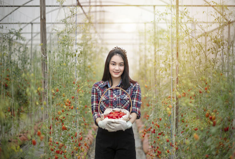 Young woman holding fruits in garden