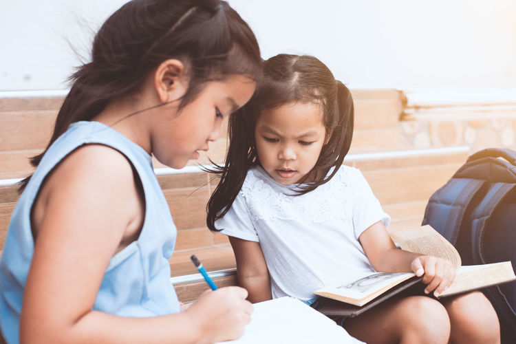 Back to school. Cute asian child girl and her sister reading a book together with fun and happiness Asian  Fun Happy Reading Siblings Sister Student Writing Back To School Backpack Bag Child Cute Daughter Enjoy Friendship Girl Kid Knowledge Learn Pupil School Smiling Study Togetherness
