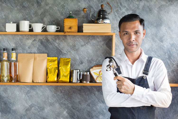 Asian man barista work on cafe Asian  Coffee Adult Arms Crossed Barista Business Cafe Confidence  Container Front View Holding Indoors  Looking At Camera Men Occupation One Person Portrait Pride Real People Shelf Standing Waist Up Young Adult