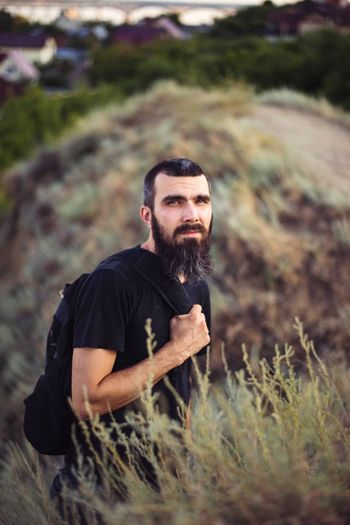 Portrait of a man with a beard on the background of nature and mountains