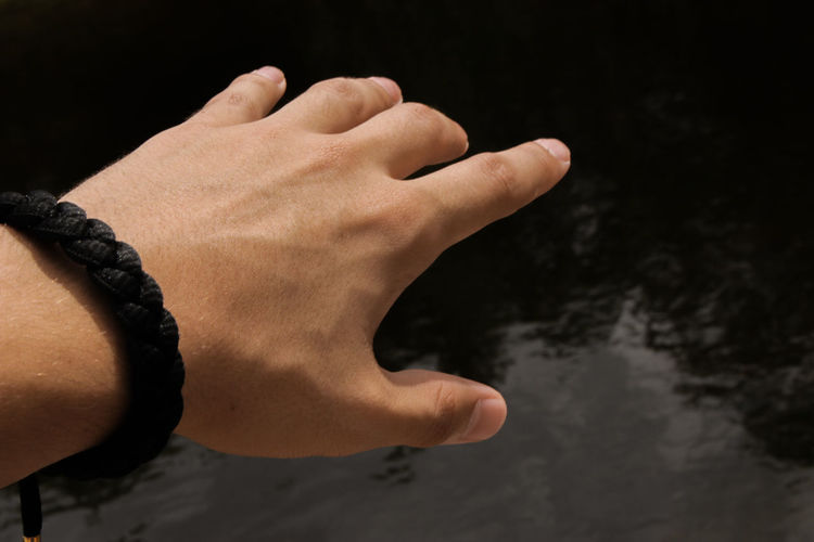 Cropped Hand Gesturing Against Pond