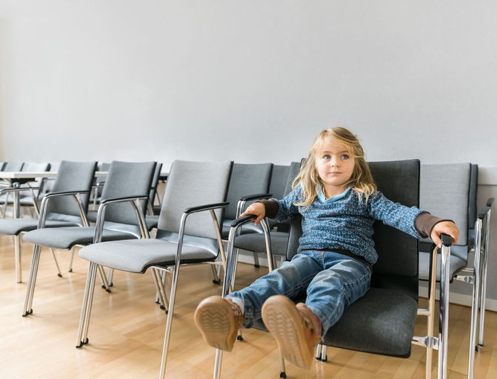 Thoughtful girl sitting on chair against white wall