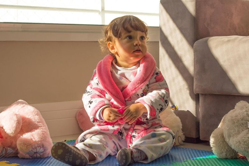 Girl looking away while sitting on pink indoors