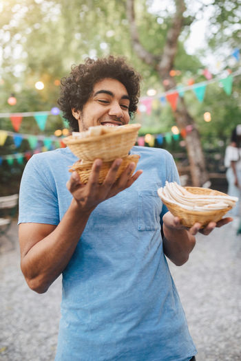 Smiling man holding ice cream standing outdoors