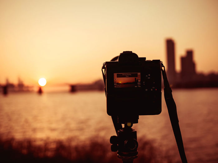 Close-up of camera against sky during sunset and bridge