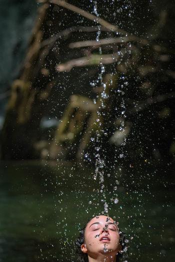Teenage girl standing under splashing water