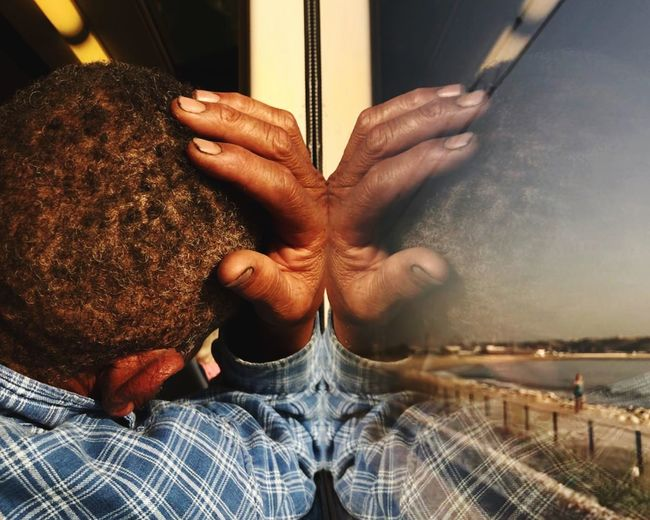 Close-up of senior man with hand on head by glass window in bus