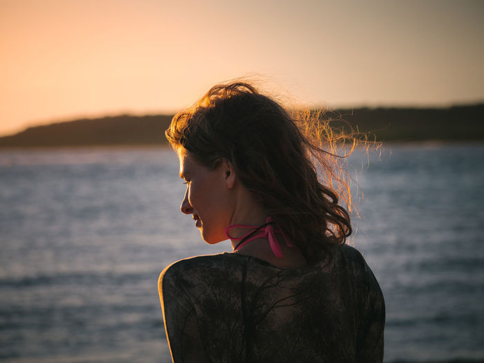 Portrait of woman standing against sea during sunset