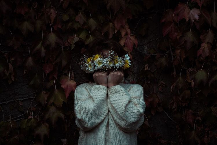Low section of person standing by flowering plants during autumn