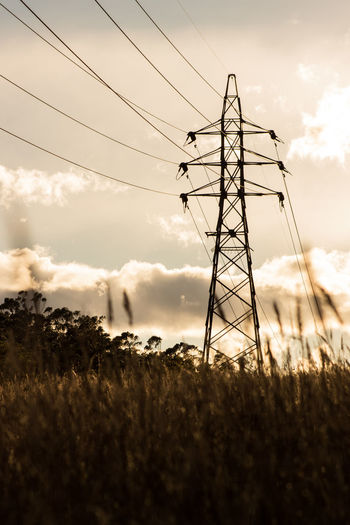 Electricity Pylon In Field Against Cloudy Sky