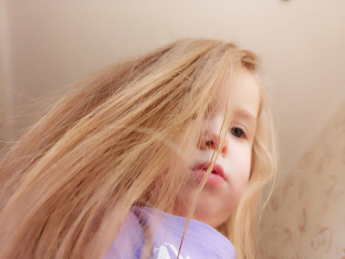 Low angle view of cute girl with blond hair at home