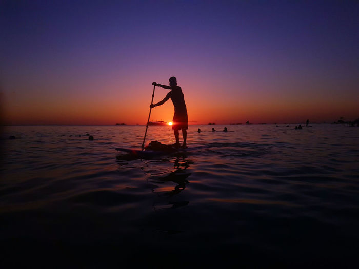 Silhouette man paddleboarding in sea against sky during sunset