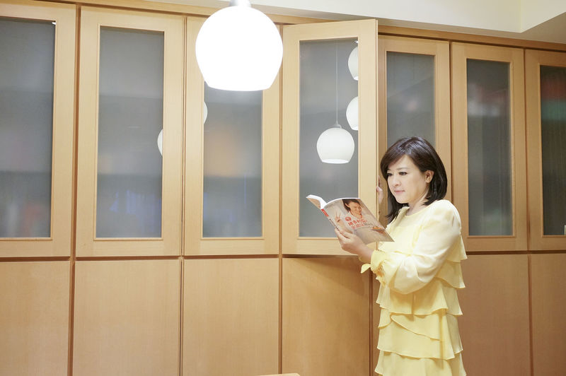 Woman Reading Magazine While Standing By Wall