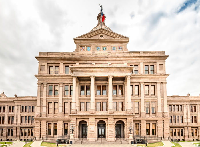 Texas State Capitol Building in Austin, with the flag of Texas Texas Capitol Austin Building State TX Capital USA Travel City History Government Tourism Law Congress Legislature  America Dome Blue House Sky Old Architecture Stone Flag Structure Star American Landmark Historic Monument United Downtown District Granite Politics Political Columns Vote Federal Building Exterior Built Structure The Past Travel Destinations Architectural Column Art And Craft No People