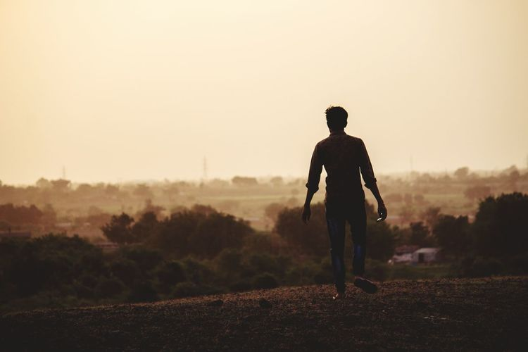 Rear view of silhouette man walking on field against sky