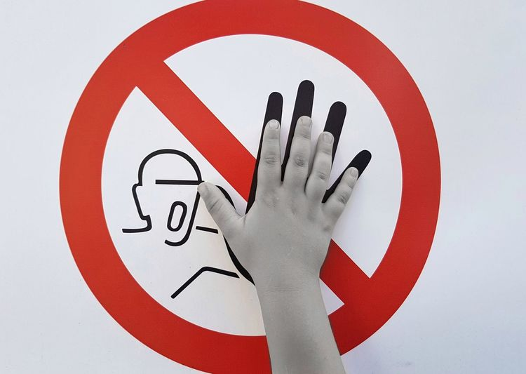 Cropped hand touching information sign against white background