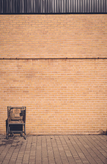 Abandoned shopping cart against brick wall