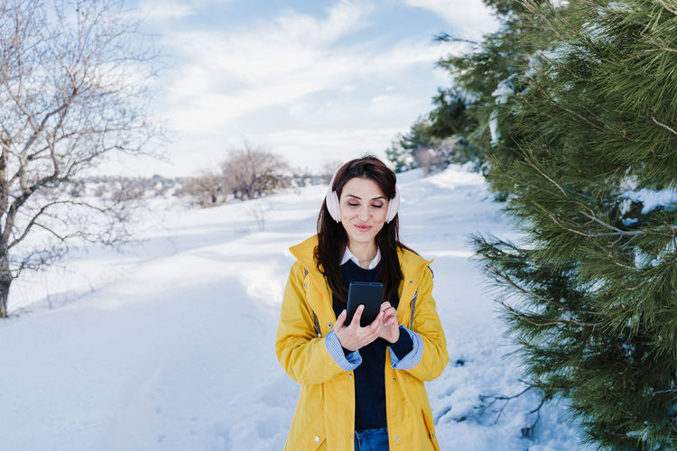 Young woman using phone while standing on snow covered tree