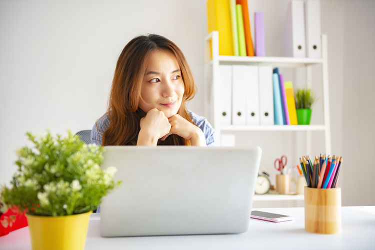 Businesswoman Looking Away While Sitting With Laptop At Desk In Office