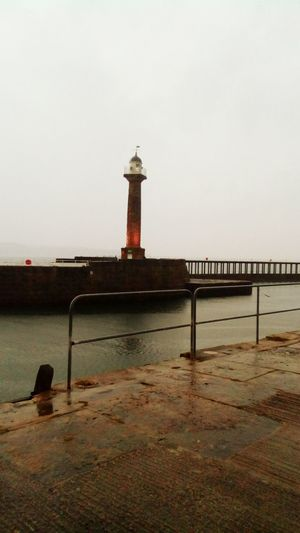 Whitby Harbour The Week On EyeEm Whitby Day Whitby North Yorkshire Harbour Harbour View Lighthouse Protection Water Sea Safety Architecture Built Structure Security Beach Building Exterior Guidance Tower Outdoors No People Sky Horizon Over Water Harbor Tranquility