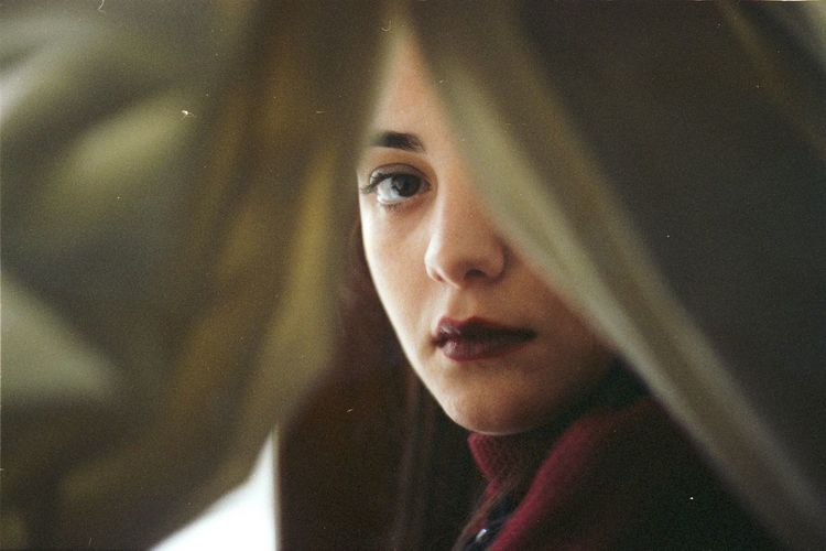 Portrait of young woman seen through curtain