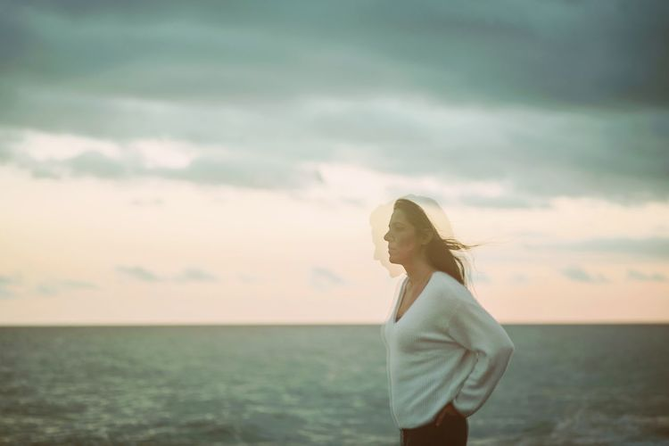 Young woman standing in sea against sky
