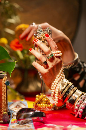 Gestures of a woman with jewelry, pearls, fruits and flowers. Abundance Wealth Celebration Art And Craft Mood Jewelry Gold Pearls Gesture Luxury Human Hand Hand Human Body Part One Person Food And Drink Focus On Foreground Indoors  Food Bracelet Adult Close-up Holding Real People Ring Human Finger Necklace Table Finger Pearl Jewelry Nail Glass