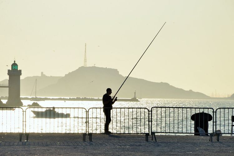 Man holding fishing rod by sea against sky during sunset